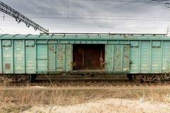 Αυτοκίνητα φορτίου φθάνει σιδηρόδρομος πλατφορμών για να εκπαιδεύσει Τραίνο στοκ εικόνες
