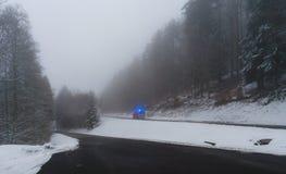Αυτοκίνητο έκτακτης ανάγκης με τα φω'τα στο χειμερινό δρόμο στο δάσος στοκ εικόνες με δικαίωμα ελεύθερης χρήσης