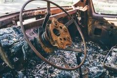 Αυτοκίνητο εγκαυμάτων έξω, μέσα στην άποψη, σκουριασμένο τιμόνι, στοκ εικόνες