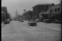 Αυτοκίνητο που γυρίζει κάτω την οδό στο στο κέντρο της πόλης Λος Άντζελες, η δεκαετία του '40 απόθεμα βίντεο