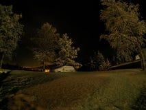 Αυτοκίνητο που θάβεται στο βαθύ νέο χιόνι τη νύχτα με τα ψηλά δέντρα Στοκ Εικόνες