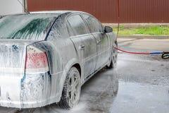 Αυτοκίνητο που καλύπτεται με τον άσπρο αφρό στο σταθμό πλυσίματος αυτοκινήτων στοκ φωτογραφίες με δικαίωμα ελεύθερης χρήσης