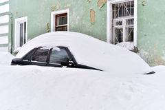 Αυτοκίνητο που καλύπτεται με το χιόνι στο προαύλιο του σπιτιού διαμερισμάτων Στοκ Φωτογραφίες