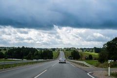 Αυτοκίνητο που κινείται επάνω στο λόφο στη εθνική οδό τη συννεφιάζω θερινή ημέρα Στοκ φωτογραφίες με δικαίωμα ελεύθερης χρήσης