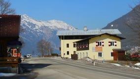 Αυτοκίνητο που περνά το ξενοδοχείο και το πρατήριο καυσίμων, τα χιονώδη βουνά και το υπόβαθρο μπλε ουρανού απόθεμα βίντεο