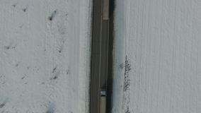 Αυτοκίνητο που προσπερνά το φορτηγό σε έναν χειμερινό δρόμο Χιονισμένος τομέας Εναέριος κάθετος πυροβολισμός απόθεμα βίντεο