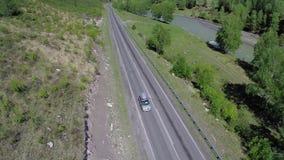 Αυτοκίνητο σε έναν δρόμο με πολλ'ες στροφές στα βουνά αλσατικό Αυτοκίνητο σε έναν δρόμο στα βουνά Το Mashina πηγαίνει στον τρόπο  απόθεμα βίντεο