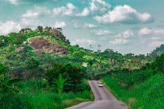 Αυτοκίνητο σε ένα πιό μακροχρόνιο τμήμα ενός εξαφανιμένος αγροτικού κράτους Νιγηρία οδικού Ekiti στοκ φωτογραφίες