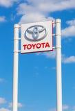 Αυτοκίνητο σημάδι αντιπροσώπων της Toyota ενάντια στο μπλε ουρανό backgroun Στοκ Εικόνες