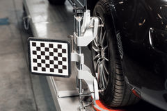 Αυτοκίνητο στη στάση με τις ρόδες αισθητήρων για τον έλεγχο κυρτώματος ευθυγράμμισης στο εργαστήριο του πρατηρίου βενζίνης Στοκ Φωτογραφίες