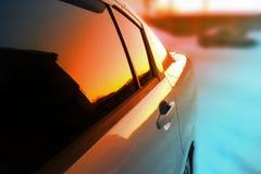 Αυτοκίνητο στο ηλιοβασίλεμα, που απεικονίζεται στους καθρέφτες στοκ εικόνα