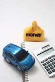 Αυτοκίνητο, χρήματα, υπολογιστής, και σημειωματάριο παιχνιδιών Στοκ Φωτογραφία