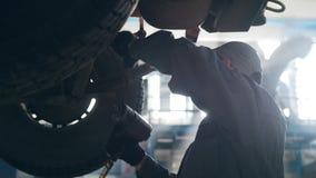 Αυτοκίνητο SUV που ανυψώνεται στην αυτοκινητική υπηρεσία για την επισκευή, καθορίζοντας ελαττώματα εργαζομένων απόθεμα βίντεο