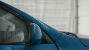 Αυτοκινήτων καθρέφτης που καλύπτεται πίσω στην κινηματογράφηση σε πρώτο πλάνο σταγονίδιων νερού, που κλείνει μια έννοια πορτών αυ φιλμ μικρού μήκους