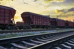Αυτοκινητάμαξα για το ξηρό φορτίο κατά τη διάρκεια του όμορφου ηλιοβασιλέματος και του ζωηρόχρωμου ουρανού, της υποδομής σιδηροδρ Στοκ Φωτογραφία
