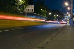 Αυτοκινητική κυκλοφορία σε μια οδό πόλεων τη νύχτα Στοκ Εικόνες