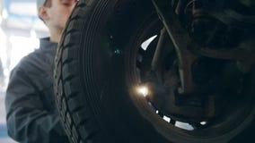 Αυτοκινητική υπηρεσία γκαράζ - ένας μηχανικός περιστρέφει τη ρόδα φιλμ μικρού μήκους