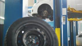 Αυτοκινητική υπηρεσία - δύο μηχανικοί που στέκονται κοντά ανυψωμένος φιλμ μικρού μήκους