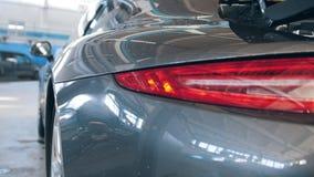 Αυτοκινητικό γκαράζ - σπορ αυτοκίνητο πολυτέλειας που αντιπροσωπεύει τον έλεγχο και την επισκευή, οπισθοσκόπο - πυροβολισμός ολισ απόθεμα βίντεο