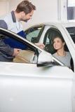 Αυτοκινητικό μηχανικό δίνοντας κλειδί αυτοκινήτων για το θηλυκό πελάτη στο κατάστημα επισκευής Στοκ φωτογραφίες με δικαίωμα ελεύθερης χρήσης
