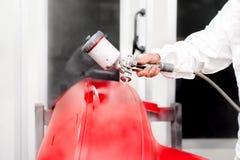 Αυτοκινητοβιομηχανία - μηχανικός που εργάζεται στη ζωγραφική ενός κόκκινου αυτοκινήτου Στοκ φωτογραφία με δικαίωμα ελεύθερης χρήσης