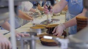 Αυτοματοποιημένη μηχανή παραγωγής κέικ Ζαχαροπλάστες που εργάζονται στα κέικ που παράγουν τον εξοπλισμό στο αρτοποιείο, γραμμή πα φιλμ μικρού μήκους