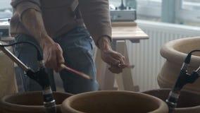 Αυτοσχεδιασμένος μουσικός που παίζει τα ξύλινα ραβδιά στα μεγάλα κεραμικά δοχεία στο εργαστήριο αγγειοπλαστικής απόθεμα βίντεο