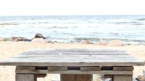 Αυτοσχεδιασμένος ξύλινος πίνακας πικ-νίκ στην αμμώδη παραλία φιλμ μικρού μήκους