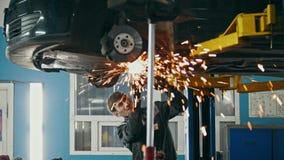 Αυτόματη υπηρεσία αυτοκινήτων - αλέθοντας κατασκευή μετάλλων εργαζομένων με ένα κυκλικό πριόνι κάτω από το κατώτατο σημείο του οχ απόθεμα βίντεο