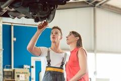 Αυτόματος μηχανικός που ελέγχει τους στροφείς φρένων δίσκων του αυτοκινήτου ενός θηλυκού πελάτη στοκ φωτογραφία με δικαίωμα ελεύθερης χρήσης