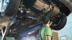 Αυτόματος μηχανικός που κοιτάζει σε ένα σπασμένο αυτοκίνητο απόθεμα βίντεο