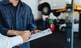 Αυτόματος μηχανικός που παίρνει το σημάδι στο έγγραφο από τον πελάτη στοκ εικόνα με δικαίωμα ελεύθερης χρήσης