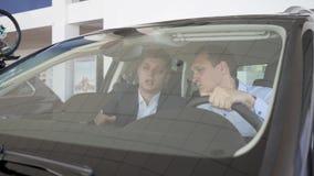 Αυτόματος παρουσιάστε, ο πωλητής και ο πελάτης κάθονται στο νέο αυτοκίνητο, συνομιλία απόθεμα βίντεο