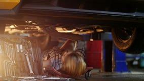 αυτόματο αυτοκίνητο μέσα στη μηχανική εργασία υπηρεσιών Νέο να βρεθεί γυναικών κάτω από το αυτοκίνητο και το σκουπίζει με ένα κου φιλμ μικρού μήκους