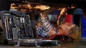 αυτόματο αυτοκίνητο μέσα στη μηχανική εργασία υπηρεσιών Νέο να βρεθεί γυναικών κάτω από το αυτοκίνητο, παίρνει ένα γαλλικό κλειδί απόθεμα βίντεο