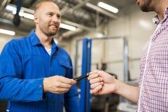Αυτόματο μηχανικό δίνοντας κλειδί αυτοκινήτων για το άτομο στο εργαστήριο Στοκ Φωτογραφία
