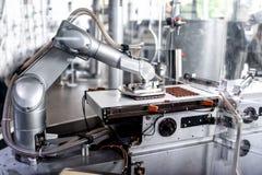 Αυτόματο ρομποτικό χέρι που κινεί τα μικροσκοπικά κομμάτια της σοκολάτας Στοκ φωτογραφία με δικαίωμα ελεύθερης χρήσης