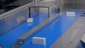 Αυτόματο ταξινομώντας σύστημα μεταφορέων - κινούμενα άσπρα μικρά κουτιά από χαρτόνι φιλμ μικρού μήκους