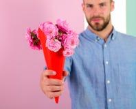 Αυτό είναι γιατί φαλλοκράτης δίνετε τα λουλούδια ως ρομαντικό δώρο Ο φίλος βέβαιος κρατά τα λουλούδια ανθοδεσμών Ο τύπος φέρνει ρ Στοκ Φωτογραφία