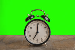 Αυτό ρολόι ` s επτά ο ` ήδη, χρόνος ξυπνήστε για το πρόγευμα, εκλεκτής ποιότητας παλαιό μαύρο μεταλλικό ξυπνητήρι στοκ φωτογραφία