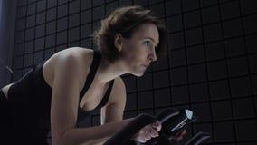 Αυτό το βίντεο είναι για την πλάγια όψη της αρκετά ελκυστικής νέας γυναίκας που απολαμβάνει το workout της στο ποδήλατο άσκησης Ό φιλμ μικρού μήκους