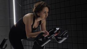 Αυτό το βίντεο είναι για την πλάγια όψη της αρκετά ελκυστικής νέας γυναίκας που απολαμβάνει το workout της στο ποδήλατο άσκησης Ό απόθεμα βίντεο
