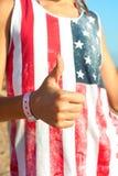 Αυτό ` s εντάξει! Νέο κορίτσι στο αμερικανικό πουκάμισο που παρουσιάζει αντίχειρα Στοκ Εικόνες