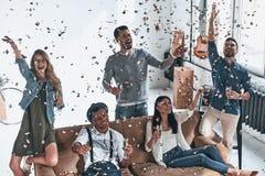 Αφήστε το κόμμα να αρχίσει Τοπ άποψη των ευτυχών νέων στο περιστασιακό W στοκ φωτογραφίες