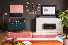 Αφίσα επάνω από την εστία στο γκρίζο εσωτερικό καθιστικών με τις εγκαταστάσεις δίπλα στο ρόδινους καναπέ και τον πίνακα στοκ φωτογραφίες