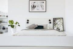 Αφίσα επάνω από το κρεβάτι στην πλατφόρμα στο άσπρο εσωτερικό κρεβατοκάμαρων με το σχέδιο στοκ εικόνες