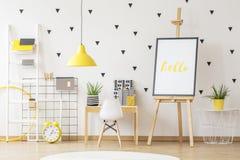 Αφίσα easel δίπλα στο ξύλινο γραφείο και άσπρη καρέκλα στο παιδί ` s ρ στοκ εικόνα