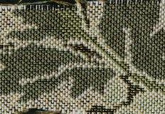 Αφαίρεση για το υπόβαθρο σκοτεινό καφετί ύφασμα με τις floral διακοσμήσεις που γίνονται από τα δασικά φύλλα Στοκ Εικόνες