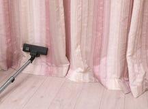 Αφαίρεση της σκόνης από τις όμορφες κουρτίνες Στοκ Εικόνες