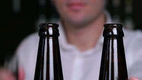 Αφαίρεση των καλυμμάτων από τα μπουκάλια της κινηματογράφησης σε πρώτο πλάνο μπύρας φιλμ μικρού μήκους